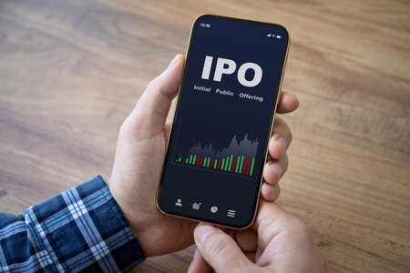 male hands hold phone with IPO stocks purchase app on screen wooden table background Stockfoto