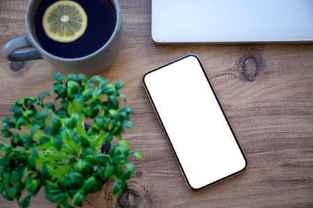 golden phone with isolated screen on wooden table in office