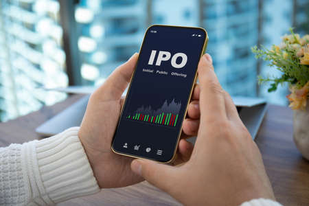 male hands hold phone with IPO stocks purchase app on screen against background of office Stockfoto