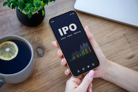 female hands hold phone with IPO stocks purchase app on screen at table in office Stockfoto