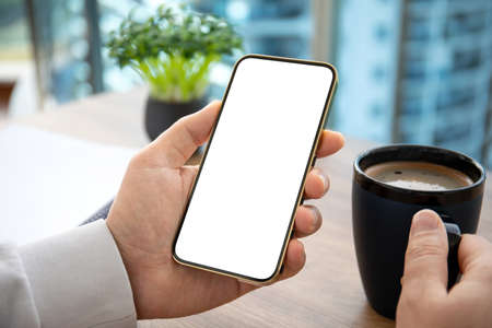 male hand holding golden phone with isolated screen on wooden table in office Stockfoto