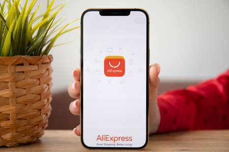Alanya, Turkey - February 25, 2021: Woman hands holding iPhone 12 Pro Max Gold with online Internet shopping service Aliexpress on the screen.