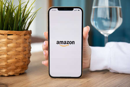 Alanya, Turkey - February 25, 2021: Woman hands holding iPhone 12 Pro Max Gold with online Internet shopping service Amazon on the screen. Redactioneel