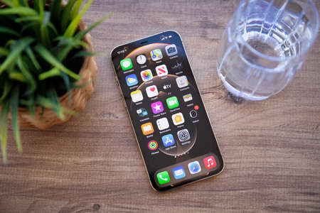 Alanya, Turkey - February 26, 2021: iPhone 12 Pro Max Gold with home screen IOS 14 on the screen on the table. iPhone 12 Pro Max Gold was created and developed by the Apple inc.