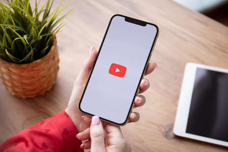 Alanya, Turkey - February 25, 2021: Woman hand holding Apple iPhone 12 Pro Max Gold with App YouTube provides streaming media and video on the screen. Redactioneel