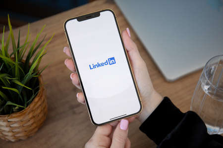 Alanya, Turkey - February 26, 2021: Woman hand holding iPhone 12 Pro Max Gold and Macbook Pro 16 with app LinkedIn in the screen.