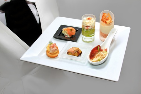Catering waiter with canapes on plate photo