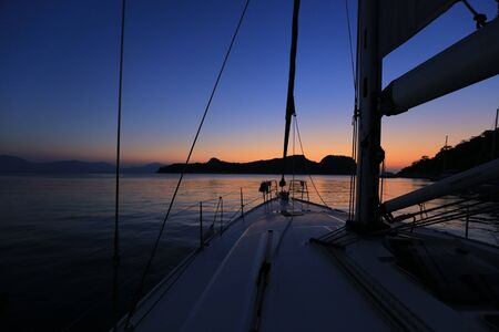 Sailing yacht moored after sunset near island in Greece Standard-Bild
