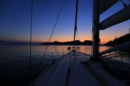Segelyacht vor Anker nach Sonnenuntergang in der Nähe der Insel in Griechenland Standard-Bild