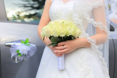 The bride holds a wedding bouquet of white roses