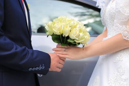 The bride and groom are holding a wedding bouquet of white roses