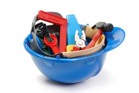 Set of plastic toy tools in blue helmet over white background Stock Photo
