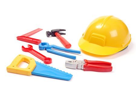 Assorted plastic toy tools and yellow helmet over white background