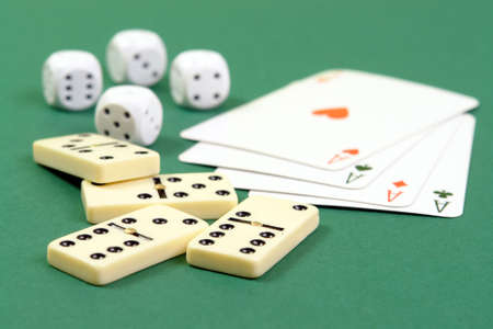 Four domino pieces, aces and dies on green table cloth photo