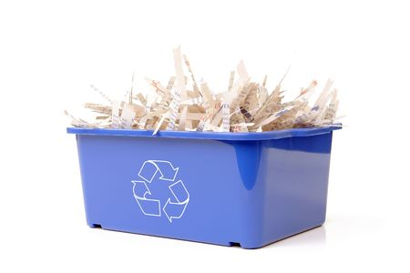 segregate: Paper cuttings in blue plastic disposal bin with white recycle symbol - over white background Stock Photo