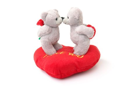 Two stuffed teddy bears kissing each other on stuffed heart-shaped pillow over white background