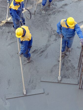 Group of construction workers spreading freshly poured concrete mix at the building site