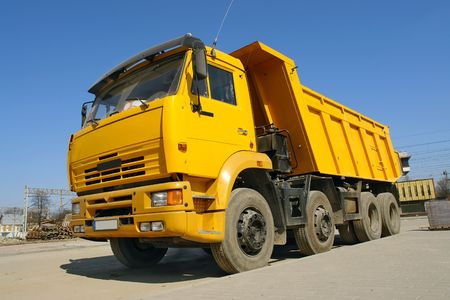 Yellow dump truck parked against clear blue sky Stock Photo