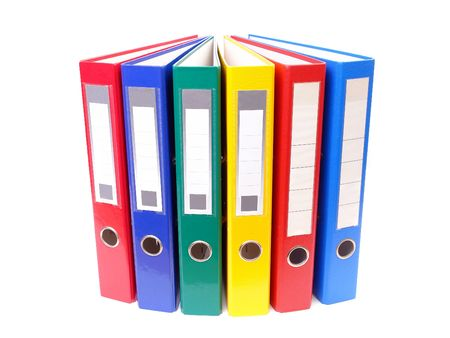 Array of colorful ring binders over white