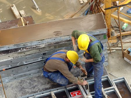Two construction workers assembling reinforcement elements