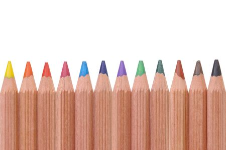 Row of twelve colorful wooden crayons over white photo