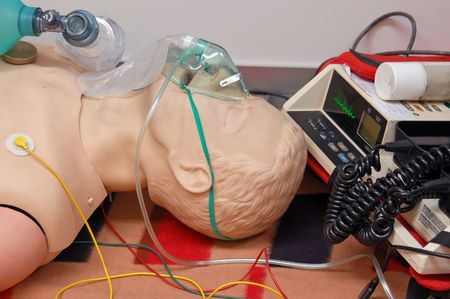 First-aid training dummy with respiratory mask and sensors connected to electrocardiograph unit