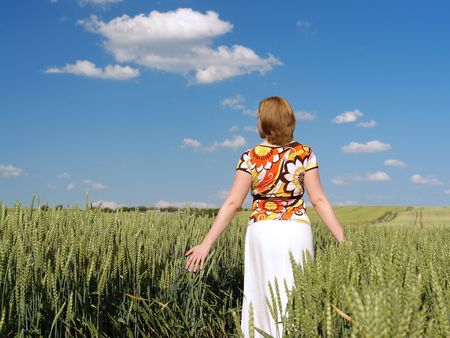 Woman wearing flowered blouse and white skirt strolling through wheat crop in dreamy mood skimming delicately corn ears with her palms photo