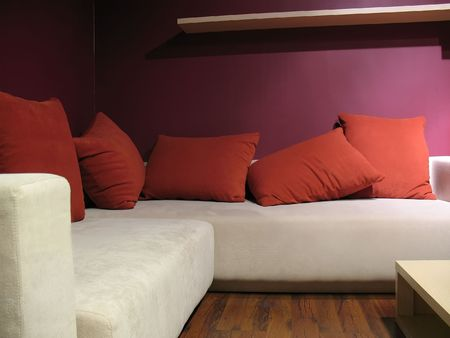 Purple wall living room with modern light beige sofa and five red pillows Stock fotó
