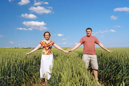 happily: Young couple holding each other with hands posing happily in cornfield Stock Photo