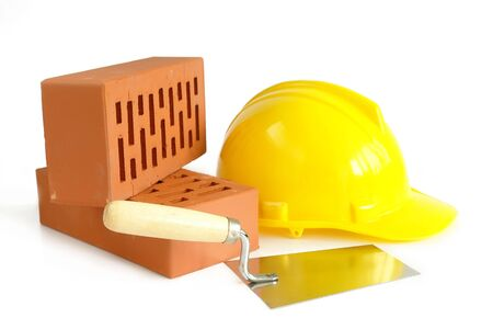Two perforated bricks, stainless steel trowel and yellow hard hat isolated on white Stock Photo - 1117768
