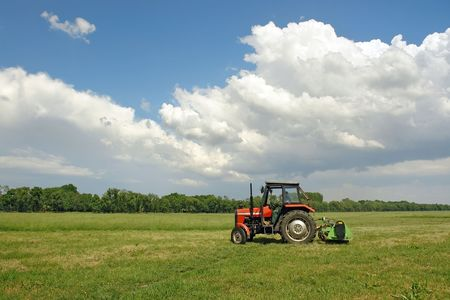 Farm tractor mowing large meadow field photo