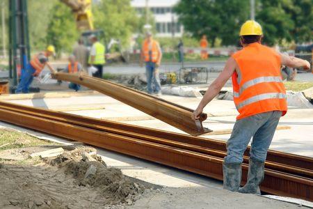 levantar peso: Tranv�a pista de los trabajadores de la construcci�n la construcci�n de nuevas trackway en el pavimento de la calle