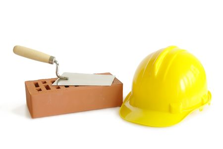 Perforated brick, stainless steel trowel and yellow hard hat isolated on white Stock Photo - 1126173