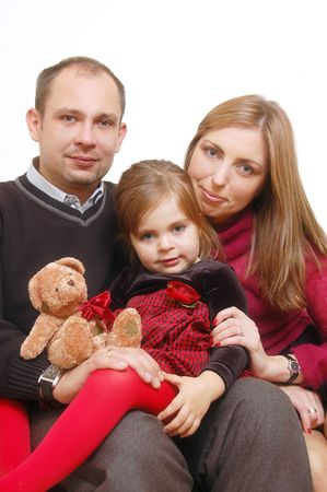Young happy married couple posing on sofa with their cute little daughter Stock Photo - 1341510