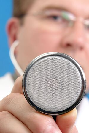 Closeup of young doctor face holding stethoscope photo