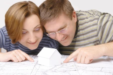 housing lot: Young couples looking closely at building plan with white little cardboard house model