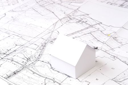 housing lot: White little cardboard house model on building plan