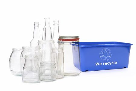 Clear glass jars and bottles and blue plastic disposal bin with white recycle symbol over white photo