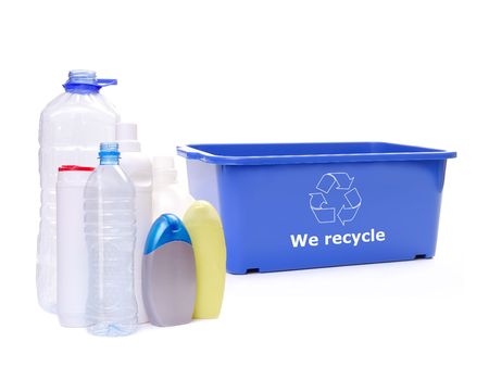 Assorted plastic bottles and blue disposal bin with white recycle symbol over white photo