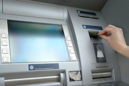 Closeup of womans hand inserting e-card into ATM slot Stock Photo