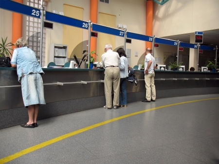 Applicants being attended at the customer service windows - content from blue information boards has been removed, so designers can put their own text there Stock Photo