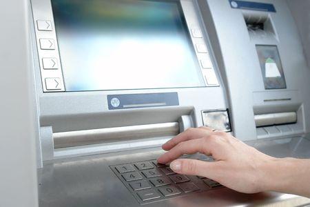 Close-up van vrouw hand PIN-code invoeren op ATM machine toetsenblok