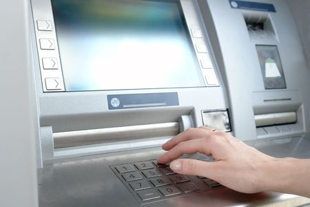 automatic teller machine bank: Closeup of womans hand entering PIN code on ATM machine keypad