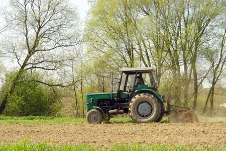 arable: Farm tractor plowing arable field in the springtime