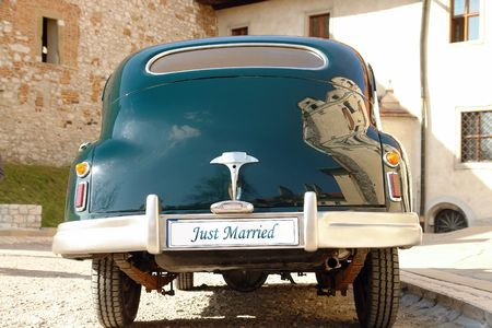 Rear of dark green retro wedding car with just married license plate photo