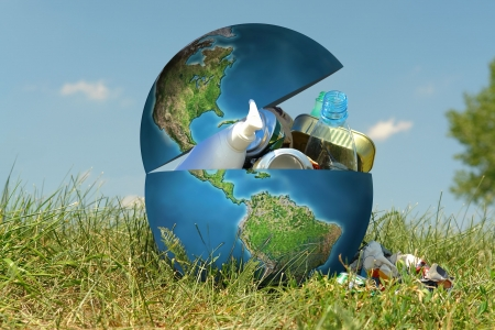 Earth globe in grass filled with assorted trash - concept representing environmental contamination of our planet by people and industry Stock Photo - 1334257