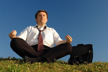 man meditating: Businessman wearing white shirt and tie meditating on grass with his shoes off over clear blue sky