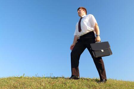 black briefcase: Empresario en camisa blanca y corbata llevar malet�n negro caminando por el c�sped sobre el terreno contra el cielo azul claro  Foto de archivo