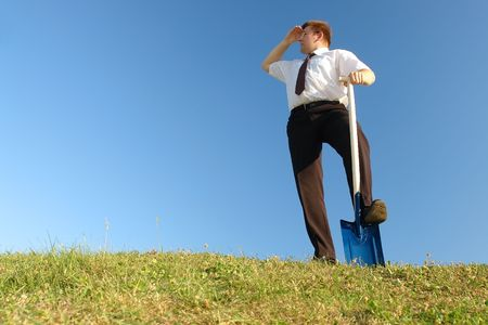 vision concept: Businessman in white shirt and tie standing in grass field over clear blue sky with one leg resting on shovel driven into grass looking sideways - business vision concept