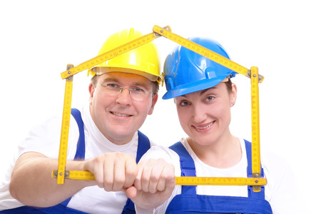 Couple wearing yellow and blue hard hats and jump suits framing themselves with yellow wooden folding ruler shaped in form of house over white background